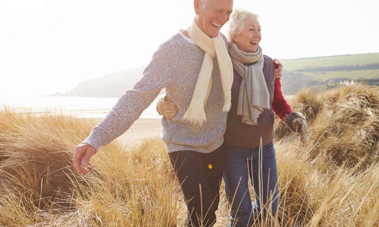 Intertwined elderly couple walking in a field