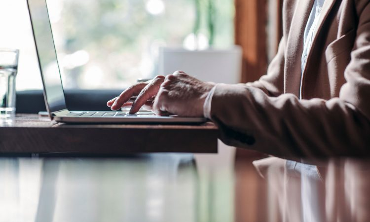 Older person writing at the computer