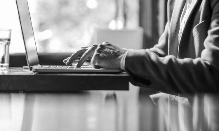 Personne âgé écrivant à l'ordinateur