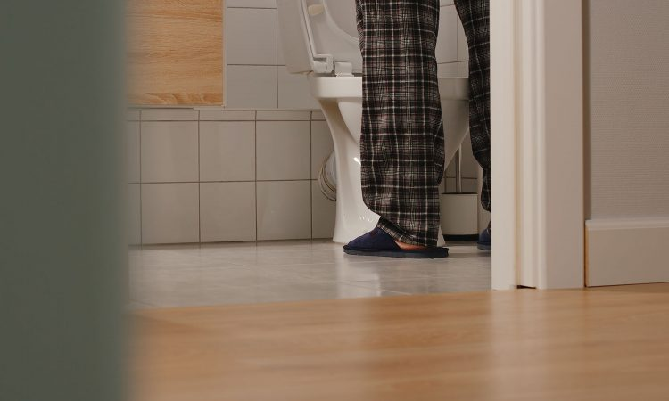 Homme debout devant la toilette