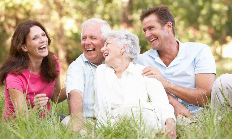 Quatre personnes assisent dans la pelouse riant