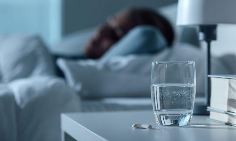 Personne qui dort en arrière-plan et en avant-plan un vers d'eau avec deux pilules
