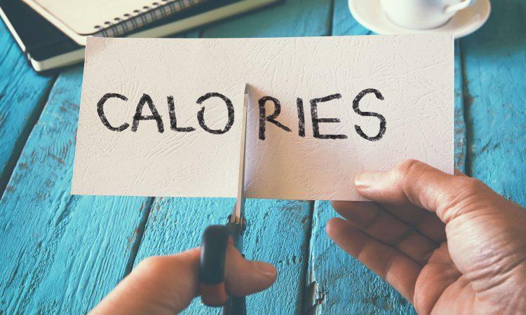 """Feuille de papier écrit """"Calories"""" qui se fait couper par des ciseaux"""