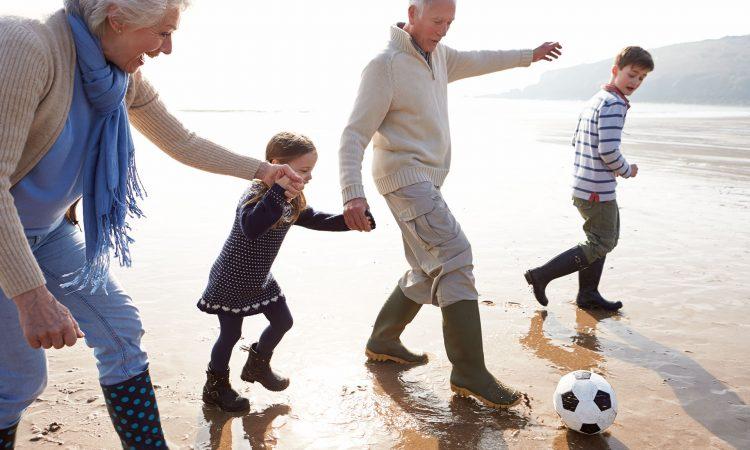 Deux personnes âgés et deux enfants jouant au ballon sur une plage