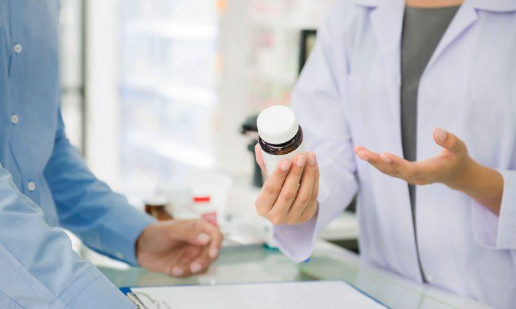 Pharmacien avec une bouteille de médicament qui parle à un client