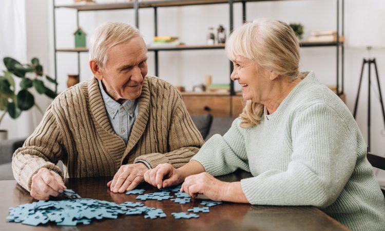 couple personnes âgées qui fait un casse-tête