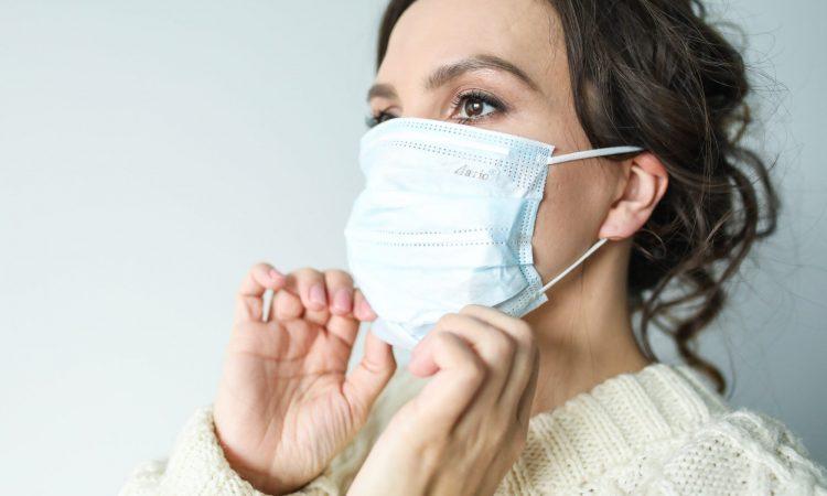 femme ajustant un masque de santé.