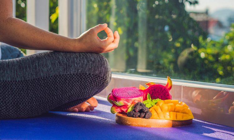femme en position de yoga avec une assiette de fruits