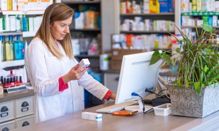 Pharmacienne qui vérifie une ordonnace à l'ordinateur.
