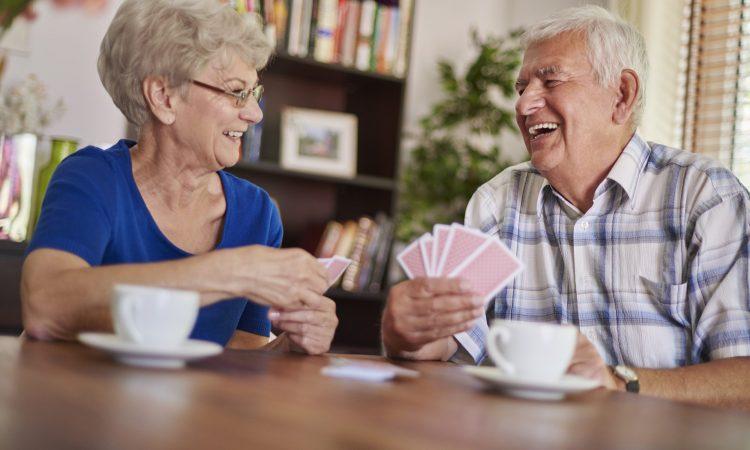 couple de personnes âgées qui jouent aux cartes