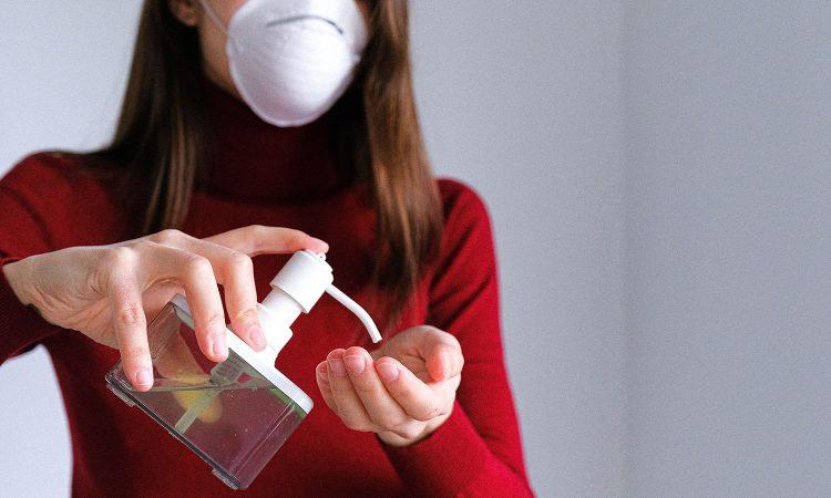 Femme portant un masque et utilisant un désinfectant pour les mains.