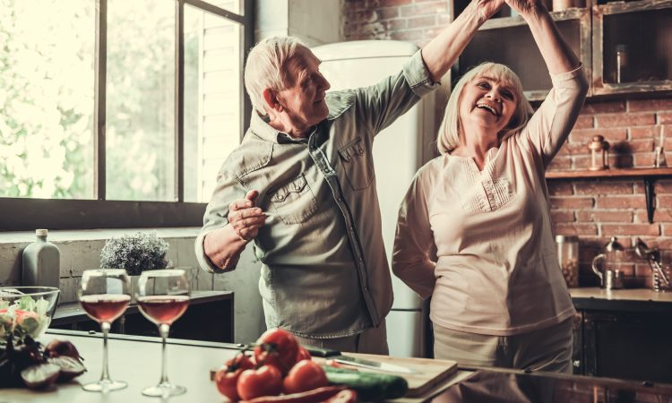couple âgé dansant dans la cuisine.