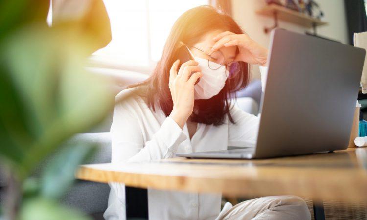 Femme avec un masque travaillant à la maison qui est stressée