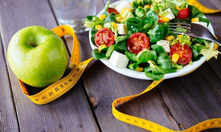 assiette de salade avec une pomme et un ruban à mesurer