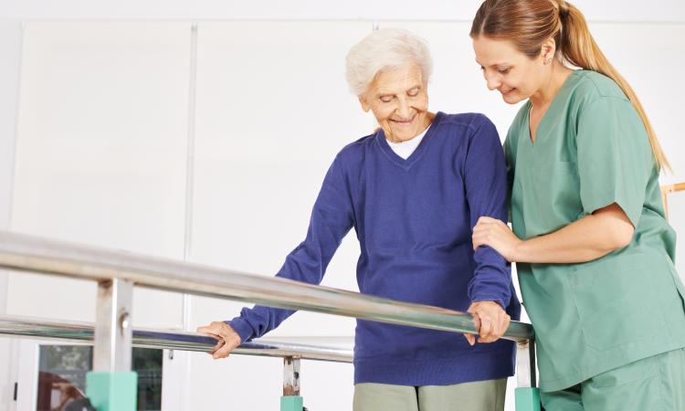 Dame âgée aidé par une physiothérapeute