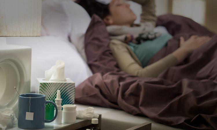 femme couchée dans son lit avec des médicaments contre le rhume et la grippe