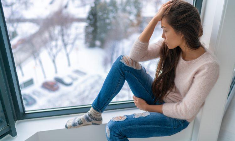 jeune femme déprimée regardant la neige par la fenêtre